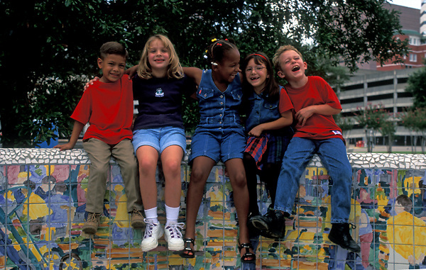 Stock photo of five young children sitting on a colorful wall