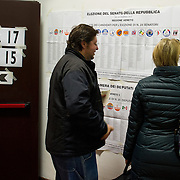 VENICE, ITALY - FEBRUARY 24: A man and a woman look at an Electora banner before casting their vote as the General Election gets underway on February 24, 2013 in Venice, Italy. Italians are heading to the polls today to vote in the elections, as the country remains in the grip of economic problems . Pier Luigi Bersani's centre-left alliance is believed to be a few points ahead of the centre-right bloc led by ex-Prime Minister Silvio Berlusconi.   (Photo by Marco Secchi/Getty Images)