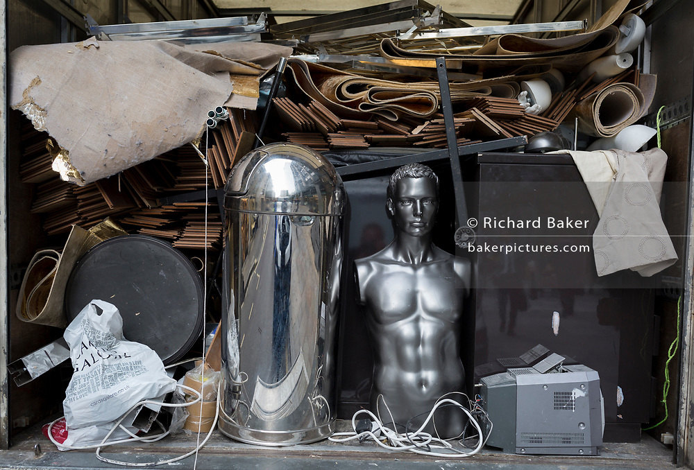 A silver male mannequin sits in the back of a lorry with other shop fittings to be junked, in the heart of the Square Mile, the capital's historical and financial centre, on 1st November 2017, in the City of London, England.