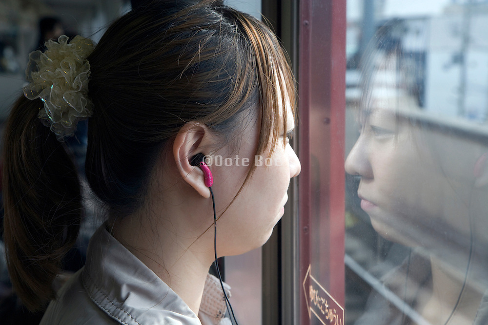 Japanese girl staring out the window while riding on a train