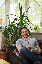 Mid adult man watching tv and drinking coffee in living room, Munich, Bavaria, Germany