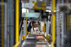 """© Licensed to London News Pictures . 04/12/2019. Manchester , UK . Packaged parcels move along a conveyor belt inside the """"MAN1"""" Amazon fulfilment centre warehouse at Manchester Airport in the North West of England . Photo credit : Joel Goodman/LNP"""