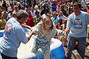 ST GEORGE, SC - APRIL 17: A young girl is helped out after rolling around in a giant vat of grits during the World Grits Festival April 17, 2010 in St. George, South Carolina. Among the various events for the festival is the Rolling in the Grits for children where the winner is the one who can hold the most of grits to their body. Grits is corn-based porridge common in the Southern United States.   (Photo Richard Ellis)
