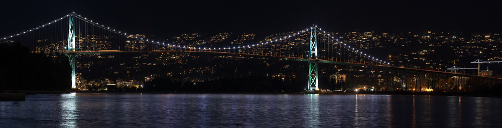 Lights illuminate the Lions Gate Bridge (opened in 1938) and the waters of Burrard Inlet at night. The Lions Gate Bridge is officially known as First Narrows Bridge and has been a National Historic Site of Canada since 2005.  Photographed from the Stanley Park seawall in Vancouver, British Columbia, Canada.