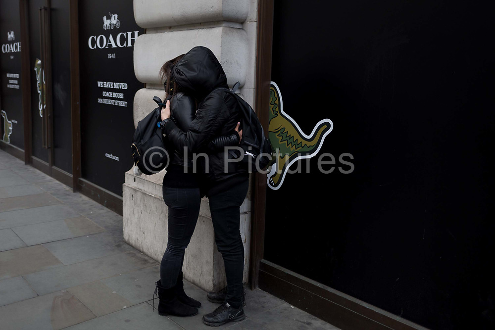 A couple wearing black hoodies with faces hidden, hug on Regent Street, on 21st March 2017, in London, England.