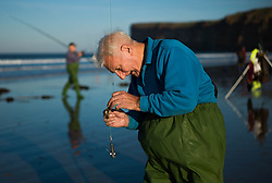 © Licensed to London News Pictures. <br /> 12/10/2014. <br /> <br /> Saltburn, United Kingdom<br /> <br /> Bill Stocker from Skelton baits his hook during the annual Jim Maidens memorial beach fishing competition in Saltburn by the Sea in Cleveland. <br /> The competition is held each year to mark the death of Saltburn plumber and keen fisherman Jim Maidens who died in 1998 when he was killed after being swept overboard from his boat 'Corina' close to the beach at Saltburn.<br /> <br /> Photo credit : Ian Forsyth/LNP