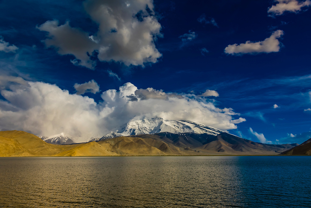 Lake Karakul  (11,811 feet) is the highest lake of the Pamir plateau, near the junction of the Pamir, Tian Shan and Kunlun mountain ranges. Surrounded by mountains which remain snow-covered throughout the year, the three highest peaks visible from the lake are Muztagh Ata (24,757 ft.) Kongur Tagh (25,025 ft.) and Kongur Tiube (24,704 ft.).The Karakoram Highway passing through the Pamir Mountains in Xinjiang China. It is the highest paved international road in the world; it connects Western China and Pakistan. It is one of the very few routes that cross the Himalayas and the most westerly of them. Historically, this was a caravan trail, one branch of the ancient Silk Road.
