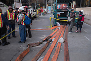 MTA workers take a break outside the Whitehall Street subway station. Orange drainage hoses snake across the sidewalk.