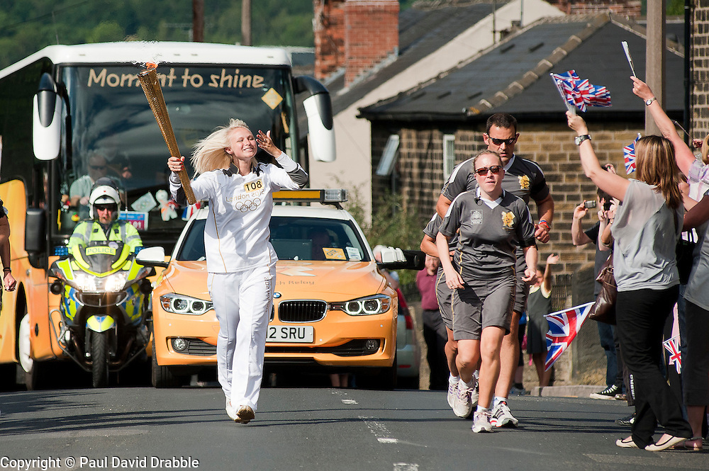 The Olympic Torch relay reaches Sheffield on day 38 coverage from the Chapeltown - Ecclesfield - Parson Cross section of the Journey.<br /> Torch bearer 108 Chloe Rutkowski aged 24 carries the flame up Church Street in her home Village of Ecclesfield<br /> 25 June 2012.<br /> Image © Paul David Drabble