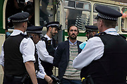 Metropolitan Police officers arrest the final Extinction Rebellion activist removed from a vintage bus used as base to block a road junction to the south of London Bridge on the ninth day of Impossible Rebellion protests on 31st August 2021 in London, United Kingdom. Extinction Rebellion are calling on the UK government to cease all new fossil fuel investment with immediate effect.