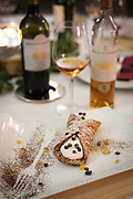 Cannoli dessert and sweet dessert wine at the table, Sicilian cuisine. Sicily, Italy.