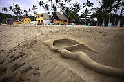 """SHOT 2/9/09 5:36:42 PM - A sand sculpture of a mermaid on the beach in Sayulita, Mexico. Sayulita is a small fishing village about 25 miles north of downtown Puerto Vallarta in the state of Nayarit, Mexico. Known for its consistent river mouth surf break, roving surfers """"discovered"""" Sayulita in the late 60's with the construction of Mexican Highway 200. Today, Sayulita is a prosperous growing village of approximately 4,000 residents. Hailed as a popular off-the-beaten-path travel destination, Sayulita offers a variety of activities such as horseback riding, hiking, jungle canopy tours, snorkeling and fishing. Still a mecca for beginner surfers of all ages, the quaint town attracts upscale tourists with its numerous art galleries and restaurants as well. Sayulita has a curious eclectic quality, frequented by native Cora and Huichol peoples, travelling craftsmen as well as international tourists. Sayulita is the crown jewel in the newly designated """"Riviera Nayarit"""", the coastal corridor from Litibu to San Blas. It's stunning natural beauty and easy access to Puerto Vallarta have made Sayulita real estate some of the most sought after in all of Mexico..(Photo by Marc Piscotty / © 2009)"""