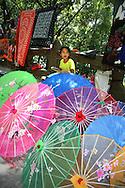 kid selling chinese umbrellas in Yangshuo