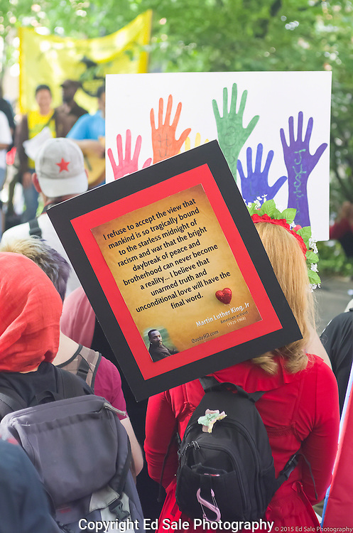 Woman holds sign at 2105 May Day Rally in Portland, Oregon with quote from Dr. Martin Luther King, Jr.  encouraging love whle sign with colorful hands is seen in the background.