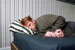Man sleeping in temporary accommodation,