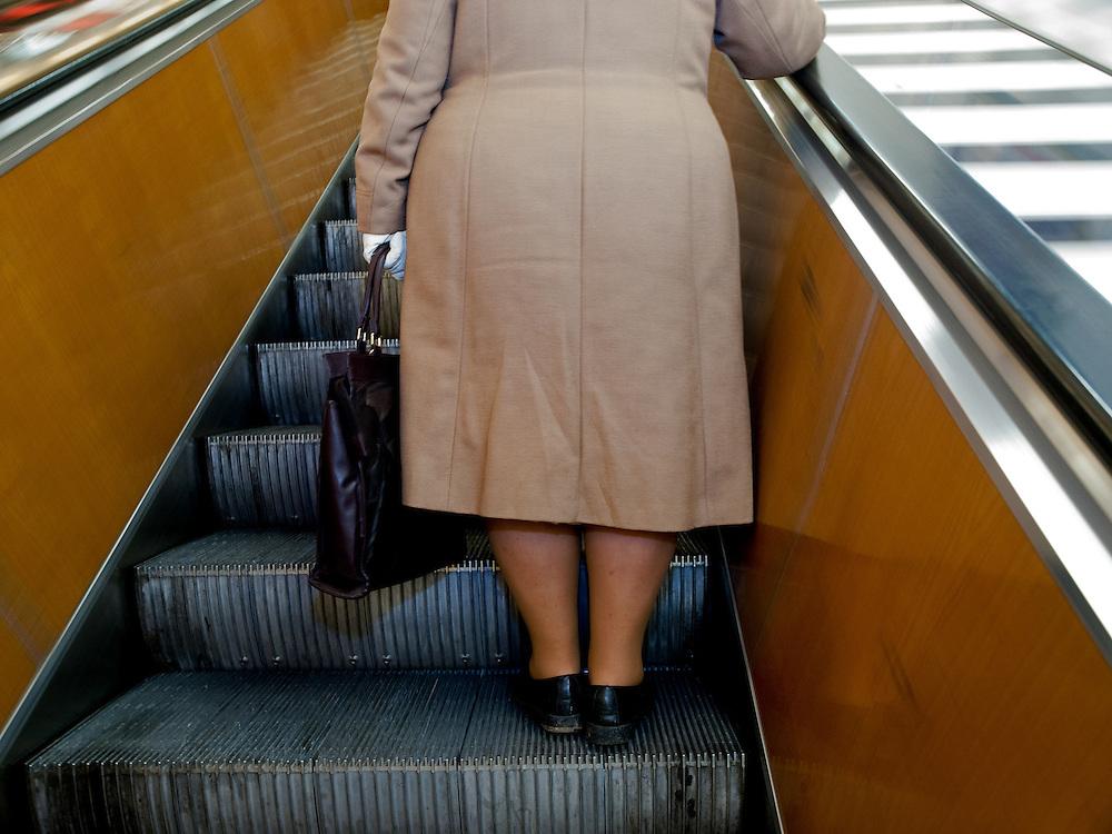 "An elderly woman leaving on an escalator the Prague subway station ""Mustek"" in the city center of Prague."