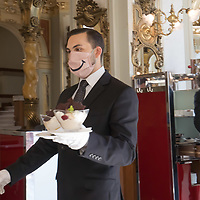 Waiter is seen serving guests at the historic downtown New York Cafe during the ease after the COVID-19 restrictions in Budapest, Hungary on June 10, 2020. ATTILA VOLGYI