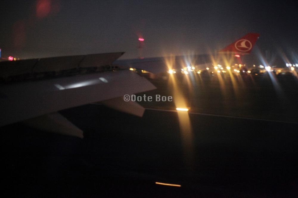 wing passenger airplane Turkish airline landing at night in Istanbul