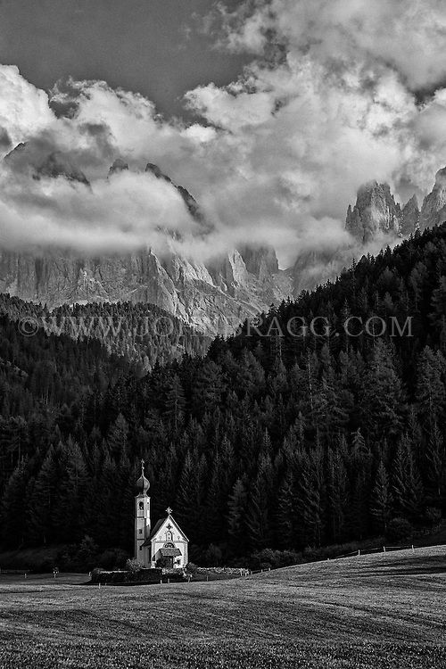 St. Johann Church in Val di Funes with the Dolomites mountain range in the distance, St. Magdalena, Italy.