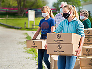 16 MAY 2020 - PERRY, IOWA:  Volunteers wait for a car during a drive through Foodbank of Iowa emergency pantry at Crossroads Church in Perry. Food insecurity has skyrocketed in Iowa because of the pandemic shutdowns. The emergency pantry in Perry distributed all 200 meal boxes in less than 45 minutes. Emergency food pantry use has more than doubled in Perry since March. The Tyson pork processing plant in Perry is the community's largest employer. It had been shut down for deep cleaning because many workers in the plant tested positive for COVID-19. Since the start of the Coronavirus (SARS-CoV-2) pandemic and resulting shutdowns, nearly 300,000 Iowans, representing 20% of the eligible workforce, have applied for unemployment benefits in Iowa. Even though the Governor has reopened the Iowa economy, the number of COVID-19 infections continues to increase.        PHOTO BY JACK KURTZ