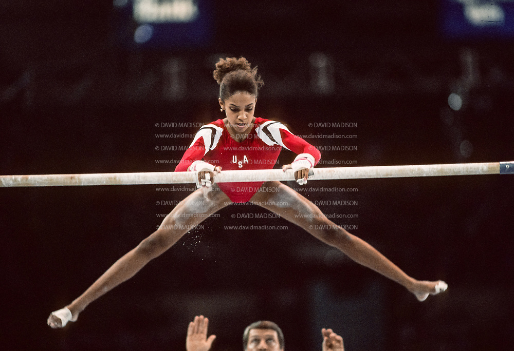 SEATTLE - JULY 1990:  Betty Okino of the United States performs on the uneven bars during the gymnastics competition of the 1990 Goodwill Games held from July 20 - August 5, 1990.   Coach Bela Karolyi of the USA is visible spotting Okino.   The gymnastics venue was the Tacoma Dome in Tacoma, Washington.  (Photo by David Madison/Getty Images)