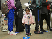 Ja'bria Williams stands between her mother, grandmother and siblings as the adults cast their votes at the start of early voting.