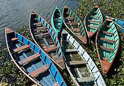 Colorful blue and green boats on Phewa Lake (or Fewa Tal), in Pokhara, Nepal.
