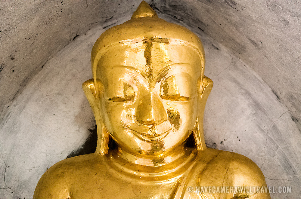 A small golden statue of The Buddha in an alcove at Thatbyinnyu Temple. Built in the 12th century, Thatbyinnyu Temple is one of the more prominent temples in the Bagan Archeological Zone and stands adjacent to the famous Ananda Temple.