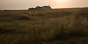 Bungalow at the coastal hamlet of Shingle Street, Suffolk, England at dawn