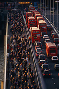 Seen from an office block high vantage point, thousands of commuters pour northwards over London Bridge against the direction of queueing buses and cars. It is a scene about the transient business community and mass transport. The working population arrives early for work over the bridge in the City of London's historic financial district. We see the sunlit faces of those walking towards the viewer which echo the red tail lights of the stationary vehicles. So gridlocked is the traffic on the southbound carriageway, there is a lone cyclist stuck and squeezed between the curb and a double-decker bus. On the other side of the road, the street is almost empty of motors adding to the drama and chaos. The City of London has a resident population of under 10,000 but a daily working population of 311,000. The City of London is a geographically-small City within Greater London, England. The City as it is known, is the historic core of London from which, along with Westminster, the modern conurbation grew. The City's boundaries have remained constant since the Middle Ages but  it is now only a tiny part of Greater London. The City of London is a major financial centre, often referred to as just the City or as the Square Mile, as it is approximately one square mile (2.6 km) in area. London Bridge's history stretches back to the first crossing over Roman Londinium, close to this site and subsequent wooden and stone bridges have helped modern London become a financial success.