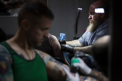 People are given tattoos during the International tattoo convention at Tobacco Dock in east London.