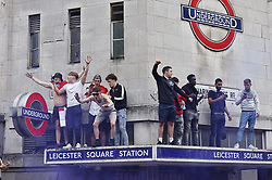 © Licensed to London News Pictures. 11/07/2021. London, UK. England supporters stand on the entrance roof of Leicester Square underground station in central London on the day of the final of EURO 2020 at Wembley where England will play Italy. Photo credit: Peter Macdiarmid/LNP