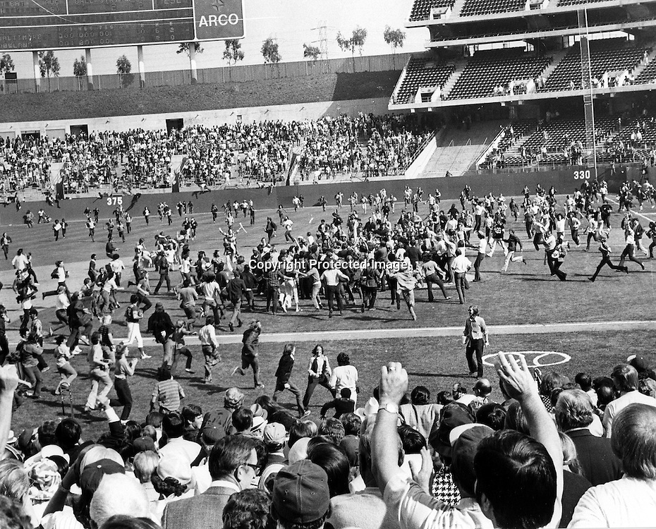 """Oakland Alameda County Coliseum...fans swarm the field after the Oakland Athletics just defeated the Baltimore Orioles to win the 1973 American League Pennant. Jim """"Catfish"""" hunter hurled a 6 hit shutout for the win. (1973 copyright/Ron Riesterer)"""