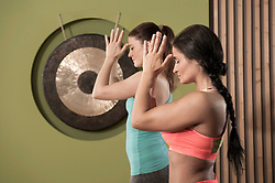 Two young women practicing yoga pose