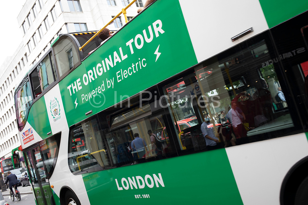 A electric powered sightseeing tour bus with the Original Tour Union jack flag branding in London, United Kingdom. Tour buses like this drive all over the capital transporting tourists to see all the sights.