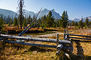 Log fence along Stanley Lake Creek, Sawtooth National Recreation Area, Idaho, USA. Hike Stanley Lake Trail to Lady Face Falls & Bridal Veil Falls (9.1 miles round trip with 1000 feet gain to both). The main trail is wide and easy, but the side trip to each falls requires scrambling with steep exposure on slippery, loose rocks. The Sawtooth Range (part of the Rocky Mountains) are made of pink granite of the 50 million year old Sawtooth batholith. Sawtooth Wilderness, managed by the US Forest Service within Sawtooth National Recreation Area, has some of the best air quality in the lower 48 states (says the US EPA), except when compromised by forest fires.