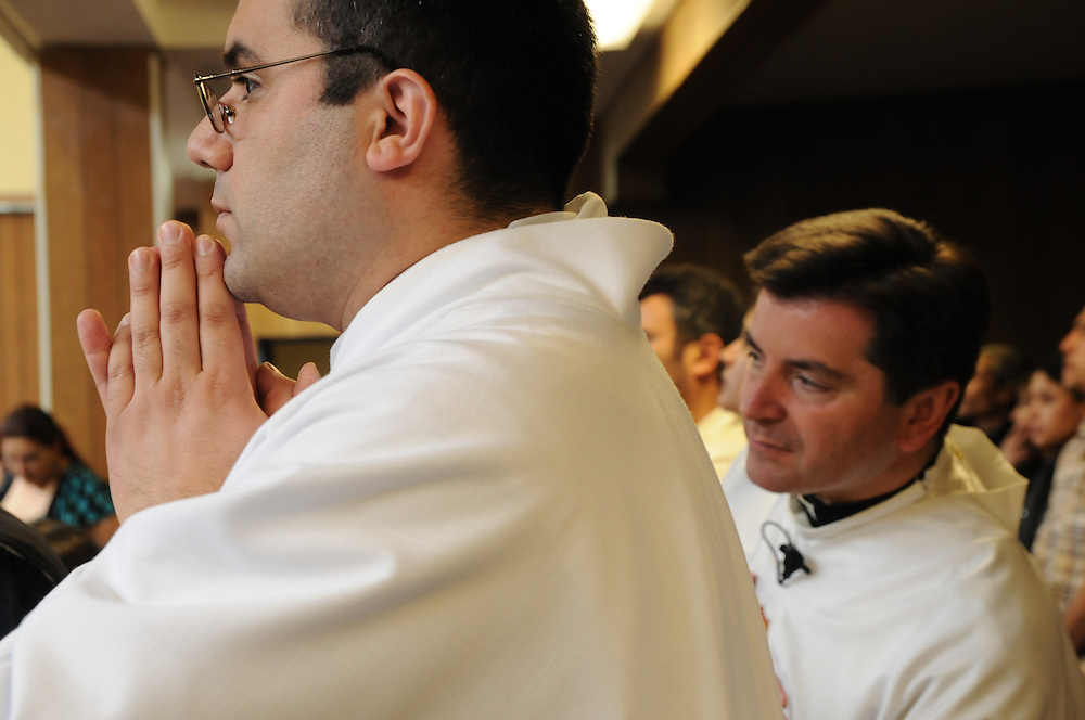 Father Franco Liporace peers past Assistant Pastor Ruben Rios from the end of the aisle as they ready to begin a mass among a crowded gymnasium at St. Francis of Assisi Catholic Church are gathered in the gymnasium for a weekly mass.