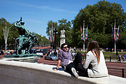 Tourists outside Buckingham Palace sitting on the Queen Victoria Memorial on a sunny spring day in London. This is a very busy area for tourism due to all the Royal architecture, gardens and statues.