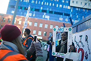 A woman shows her support by posing for a framed photograph. Junior doctors and supporters picket the Royal London Hospital in Tower Hamlet to raise support. Junior doctors all over the country are on a one day strike against the proposed new working conditions and pay by the Government.