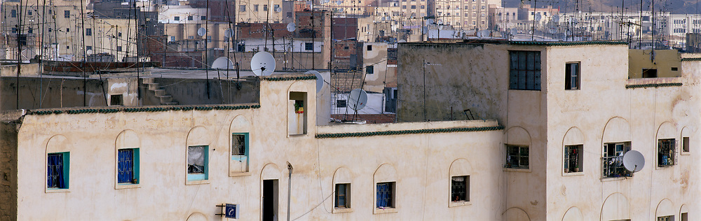 Dense city buildings with satellite dishes on rooftops