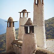 Chimneys on top of a building in Alpujarras de la Sierra, Spain, near the Sierra Nevada National Park.<br /> <br /> + ART PRINTS +<br /> To order prints or cards of this image, visit:<br /> http://greg-stechishin.artistwebsites.com/featured/andalucia-chimneys-greg-stechishin.html