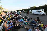 Migrants rest at the side of the motorway as hundreds of them walk from Budapest north towards Austria September 4, 2015.