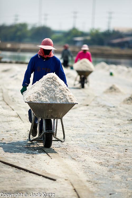 """28 MARCH 2014 - NA KHOK, SAMUT SAKHON, THAILAND:  Thai workers haul salt to a warehouse in Samut Sakhon province.Thai salt farmers south of Bangkok are experiencing a better than usual year this year because of the drought gripping Thailand. Some salt farmers say they could get an extra month of salt collection out of their fields because it has rained so little through the current dry season. Salt is normally collected from late February through May. Fields are flooded with sea water and salt is collected as the water evaporates. Last year, the salt season was shortened by more than a month because of unseasonable rains. The Thai government has warned farmers and consumers that 2014 may be a record dry year because an expected """"El Nino"""" weather pattern will block rain in mainland Southeast Asia. Salt has traditionally been harvested in tidal basins along the coast southwest of Bangkok but industrial development in the area has reduced the amount of land available for commercial salt production and now salt is mainly harvested in a small parts of Samut Songkhram and Samut Sakhon provinces.   PHOTO BY JACK KURTZ"""