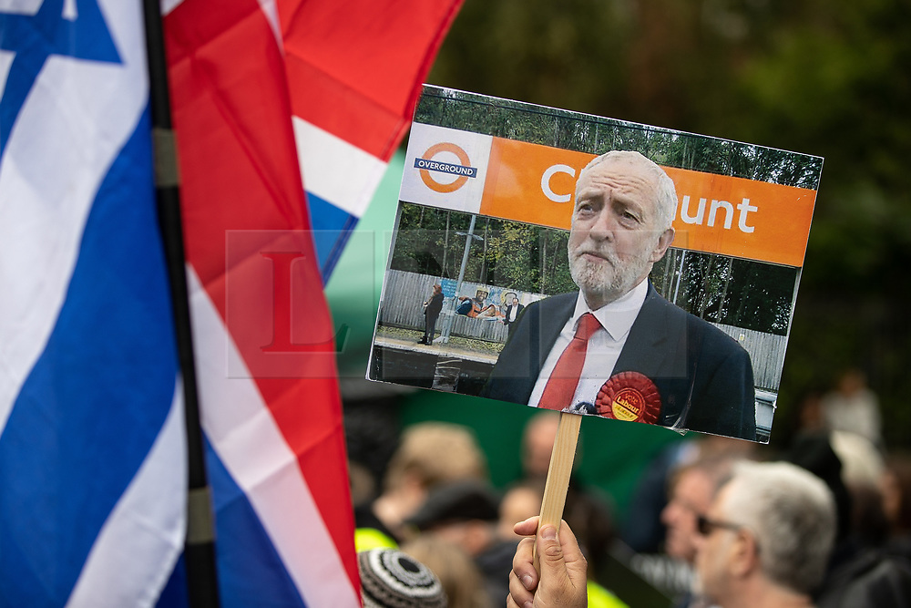 """© Licensed to London News Pictures . 16/09/2018. Manchester, UK. A placard with a photograph of Jeremy Corbyn at Cheshunt station with letters obscured by the Labour leader's head so as to read """" Cunt """" . Thousands of people including the UK's Chief Rabbi and several Members of Parliament attend a demonstration against rising anti-Semitism in British politics and society , at Cathedral Gardens in Manchester City Centre . Photo credit : Joel Goodman/LNP"""