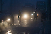 Pedestrians cross in front of commuter traffic at dawn on a foggy morning in south London.