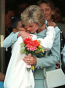 Princess Diana hugs a school child on a visit to Chicago.