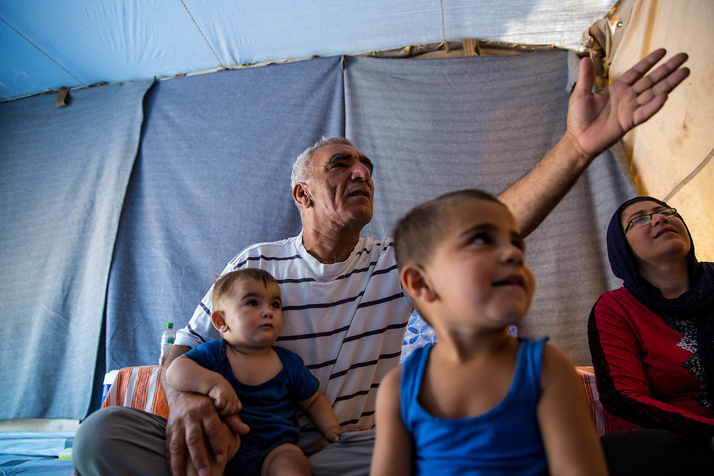 """Jameel sits with his grandson, Deyar, 1, on his lap, a neighbor to the right and his grandson and namsake, Jameel, in the foreground. They are Syrian Kurdish refugees from Aleppo. Jameel and his extended family have been in Ritsona for four months. With dwindling hope Jameel said, """"We will go anywhere as long as we can stay together."""" Ritsona Refugee Camp, Greece, July 2016."""