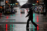 Heavy rain falls on pedestrians as they cross the street at the intersection of Sixth and Pine in downtown Seattle. (Ellen M. Banner / The Seattle Times)