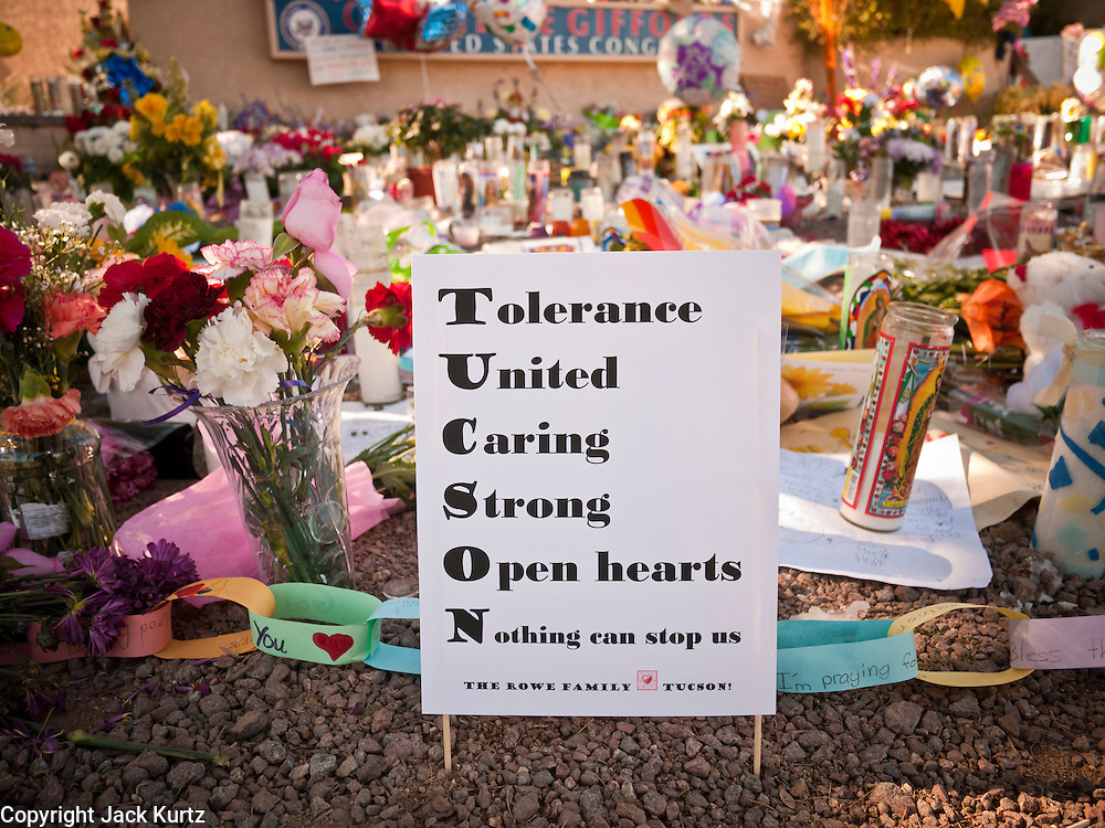 """15 JANUARY 2010 - TUCSON, AZ:   The memorial at Congresswoman Gabrielle Giffords office for victims of the mass shooting in Tucson, AZ, Saturday, January 15. Six people were killed and 14 injured in the shooting spree at a """"Congress on Your Corner"""" event hosted by Arizona Congresswoman Gabrielle Giffords at a Safeway grocery store in north Tucson on January 8. Congresswoman Giffords, the intended target of the attack, was shot in the head and seriously injured in the attack but is recovering. Doctors announced that they removed her breathing tube Saturday, one week after the attack. The alleged gunman, Jared Lee Loughner, was wrestled to the ground by bystanders when he stopped shooting to reload the Glock 19 semi-automatic pistol. Loughner is currently in federal custody at a medium security prison near Phoenix.     PHOTO BY JACK KURT"""