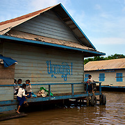 Students stand on the porch of their primary school during recess in the floating village of Chong Kneas just outside of Siem Reap, Cambodia.